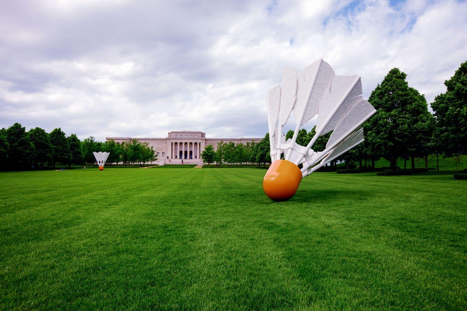 volant de badminton géant sur une pelouse avec un bâtiment du Nelson Atkins Art Museum au fond